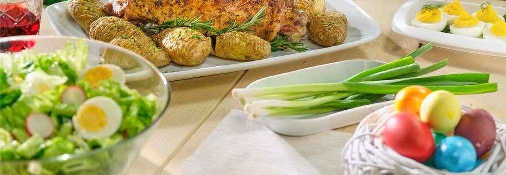 Изображение на маса с различни храни, приготвени специално за Великден, сред боядисани яйца и агнешко