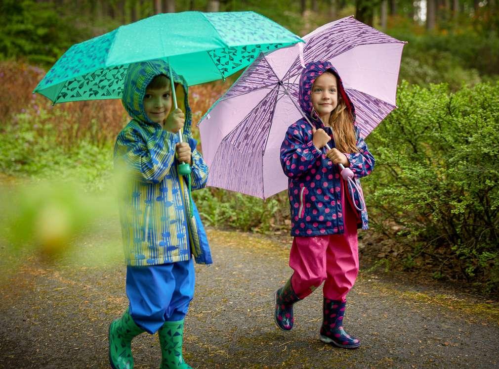 Изображение на момиченце и момченце, които се разхождат в дъжда с дъждобрани, гумени ботуши и чадъри. Нашите марки: Hip & Hopps® – богат избор