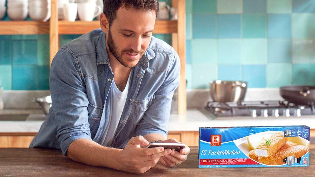 Мъж с мобилен телефон и опаковка рибни филенца нa K-Classic