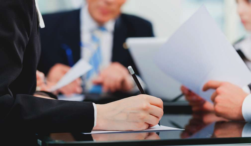 ръка подписва документи с писалка
