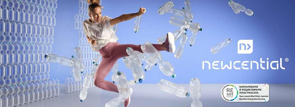 Изображение на жена, облечена в дрехи NEWCENTIAL, която рита стена, направена от пластмасови бутилки