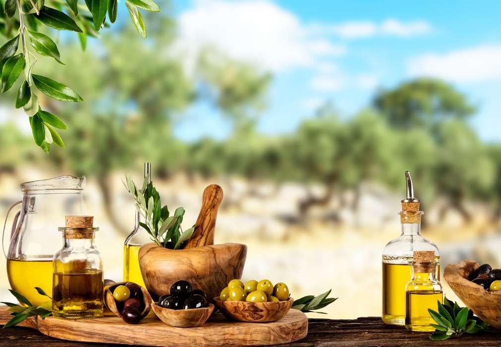 Изображение на маса, отрупана с различни видове маслини и маслиново масло