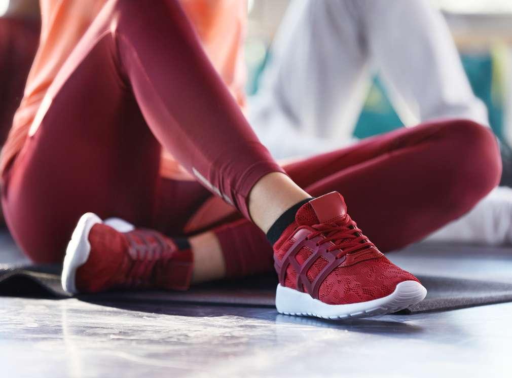 Изображение на женски крака в червен спортен клин и маратонки Newcential®