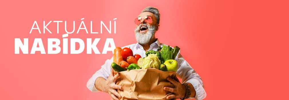 Muž drží plnou tašku s potravinami plnou čerstvých potravin