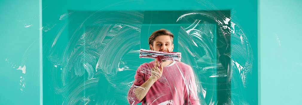 Изображение на мъж, който мие прозорец.