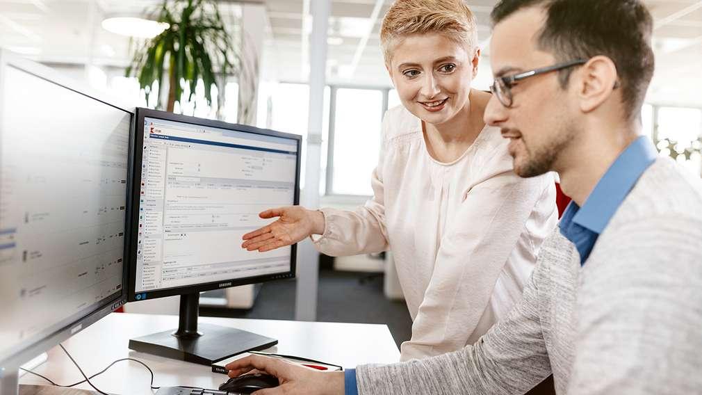 Zwei IT-Supporter schauen auf zwei Bildschirme und besprechen die weitere Vorgehensweise eines Projekts.