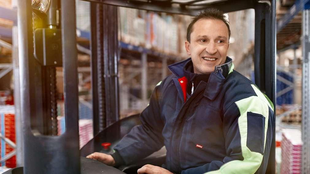 Ein Staplerfahrer transportiert Ware mit seinem Gabelstapler im Hochregallager des Logistik-Verteilzentrums.