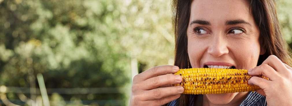 Frau mit gegrilltem Maiskolben