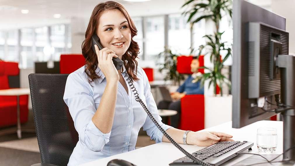 Auszubildende beantwortet eine telefonische Kundenanfrage.