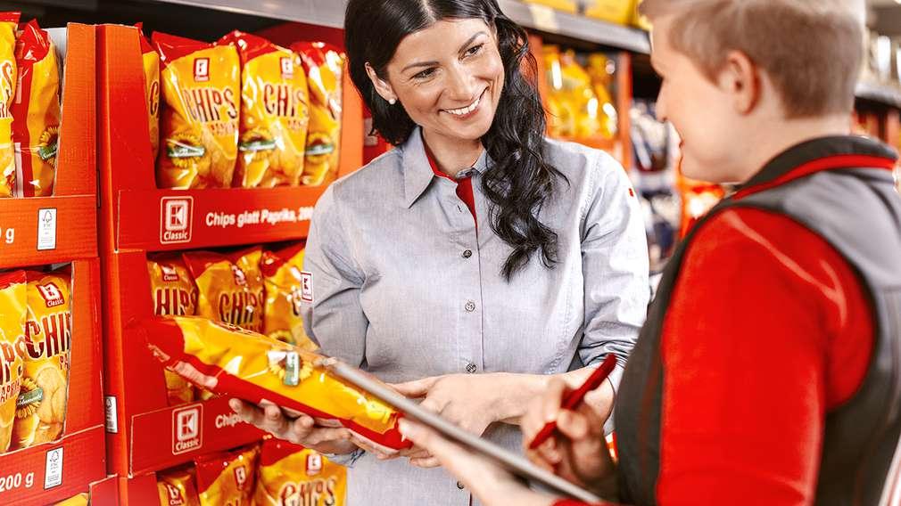 Die Leiterin eines Warenbereichs steht vor einem Regal mit ihrer Mitarbeiterin und bespricht die Warenpräsentation.