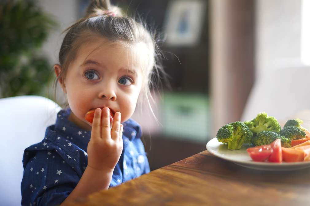 Mädchen isst Gemüse