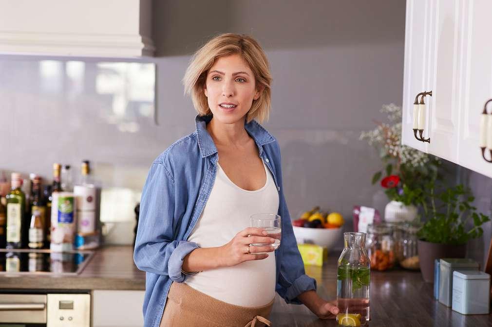 Schwangere trinkt Wasser in der Küche