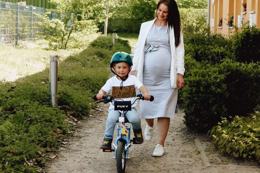 Mutter begleitet ihr Kind beim Fahrradfahren