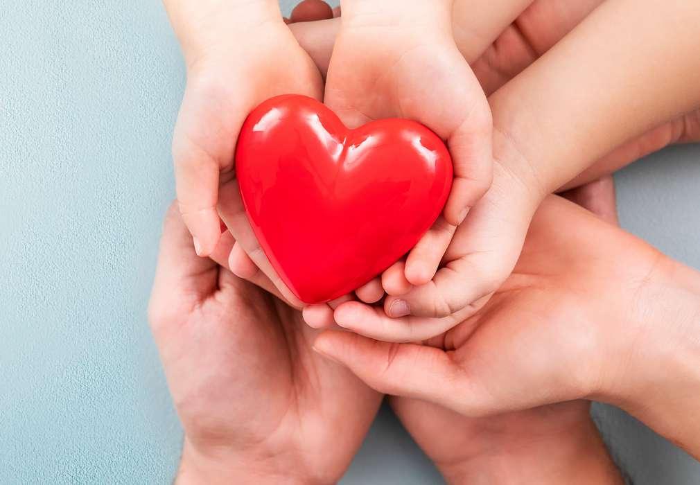 Hände von Kindern, Vater und Mutter halten gemeinsam Herz