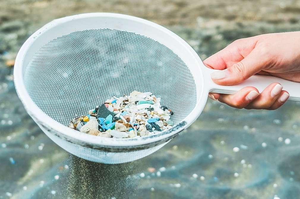 Hand hält Sieb mit Mikroplastikteilchen aus Gewässer