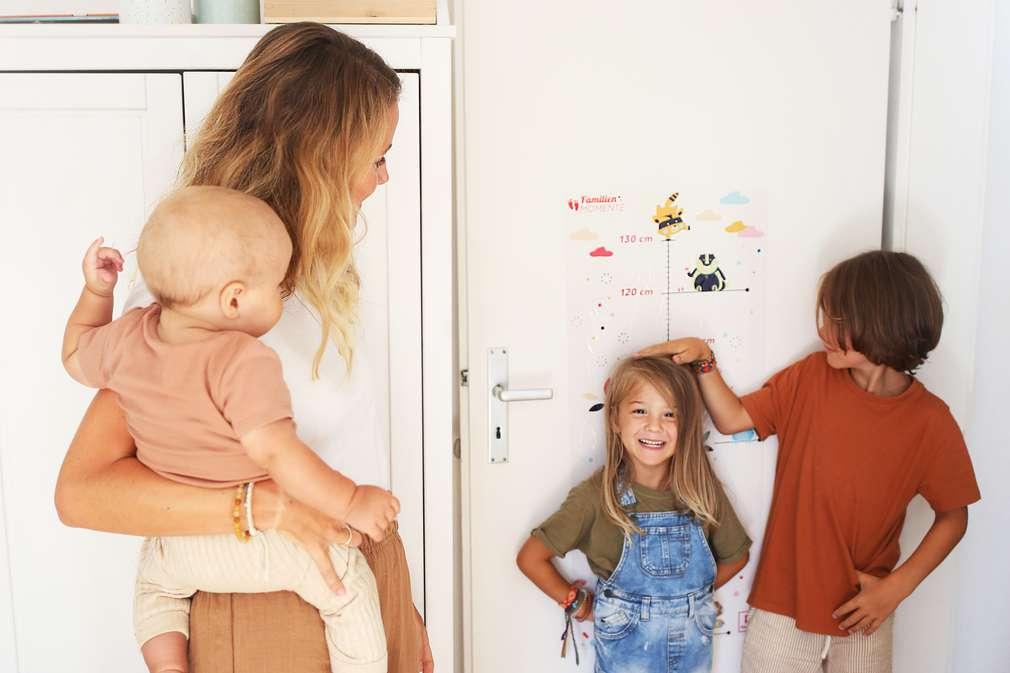 Mutter hält Baby im Arm während zwei Geschwister ihre Körpergröße an der Tür messen