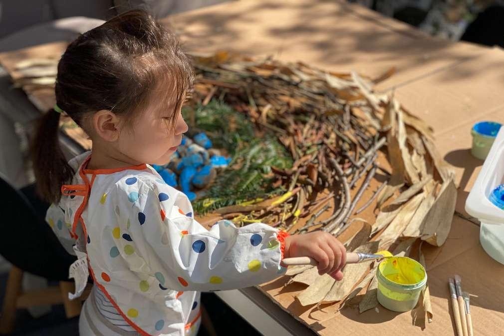 Kind bastelt einen Regenbogen aus Blätter, Ästen und Steinen