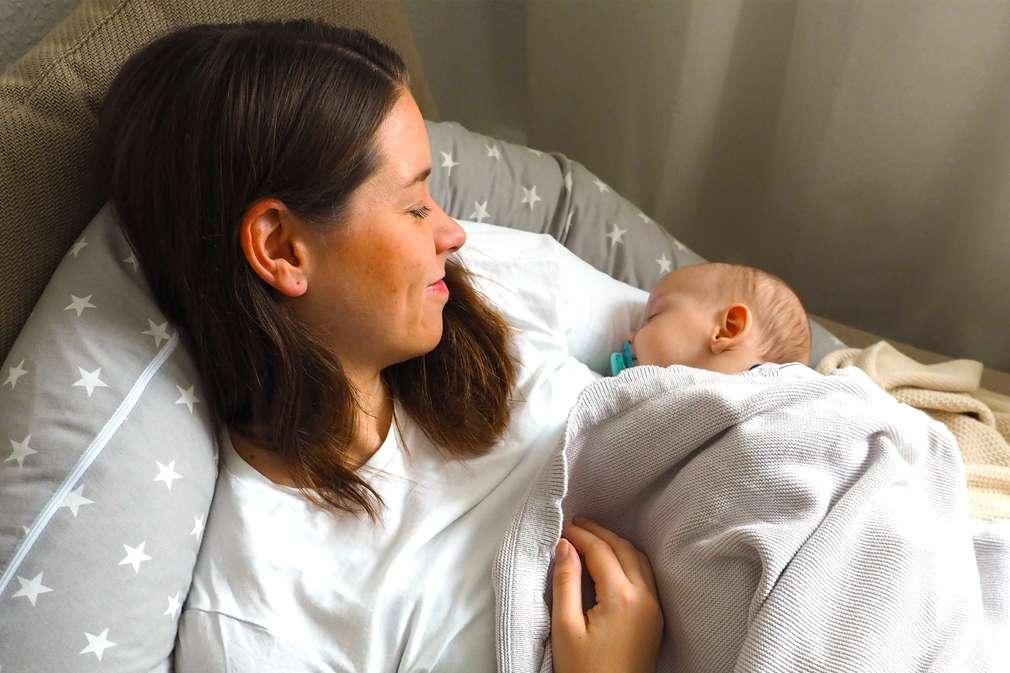 Mutter liegt mit ihrem neugeborenen Kind im Bett