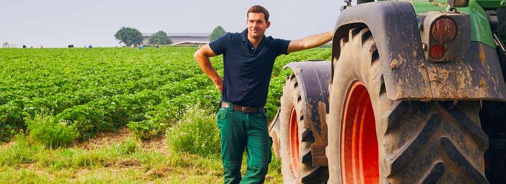 Bauer lehnt an Traktor auf einem Feld