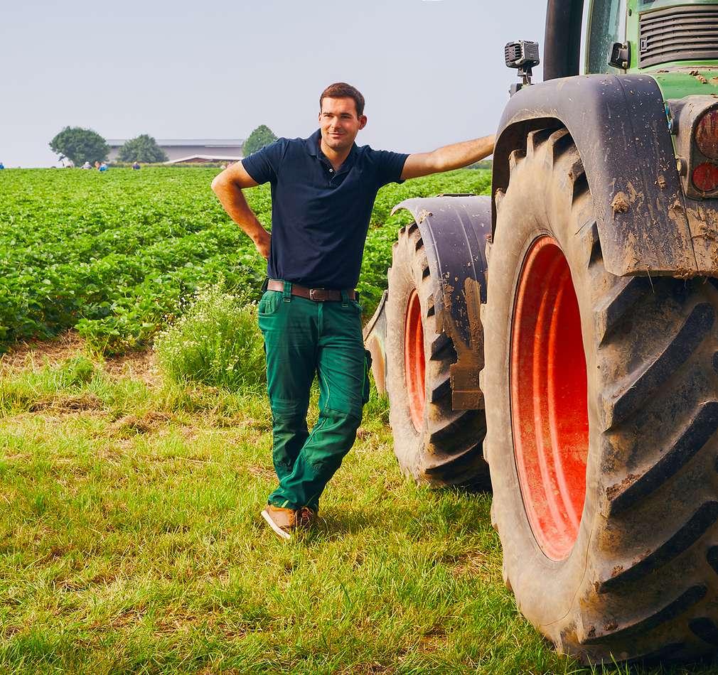 Bauer lehnt sich an Traktor auf einem Feld