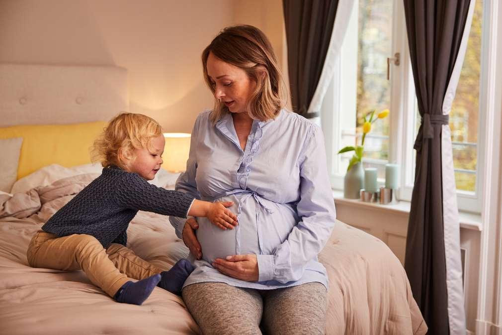 Schwangere sitzt mit Sohn auf dem Bett