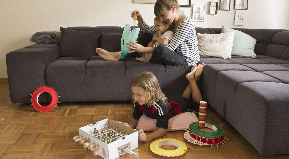 Mutter und Kinder spielen im Wohnzimmer