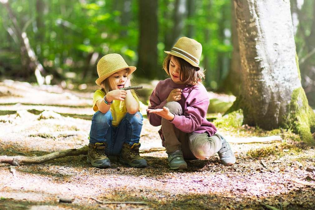 Kinder sitzen auf dem Boden im Wald