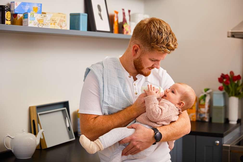 Vater gibt Baby die Flasche