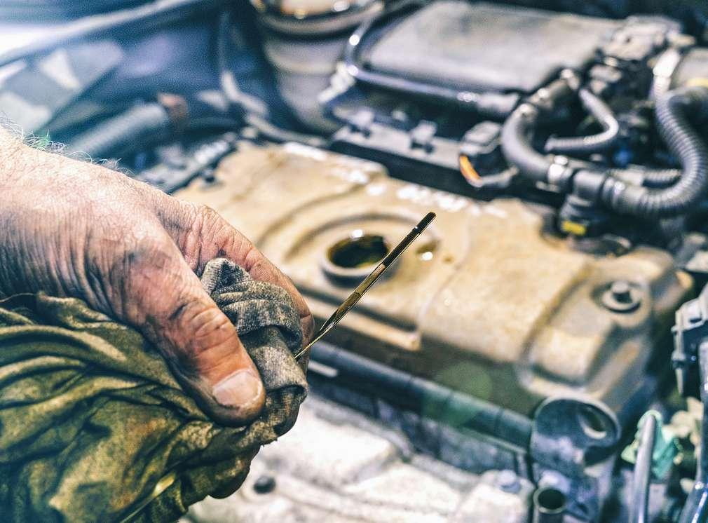 In einer Hand wird ein Ölstab gehalten. Im Hintergrund ist die Motorhaube zu sehen.