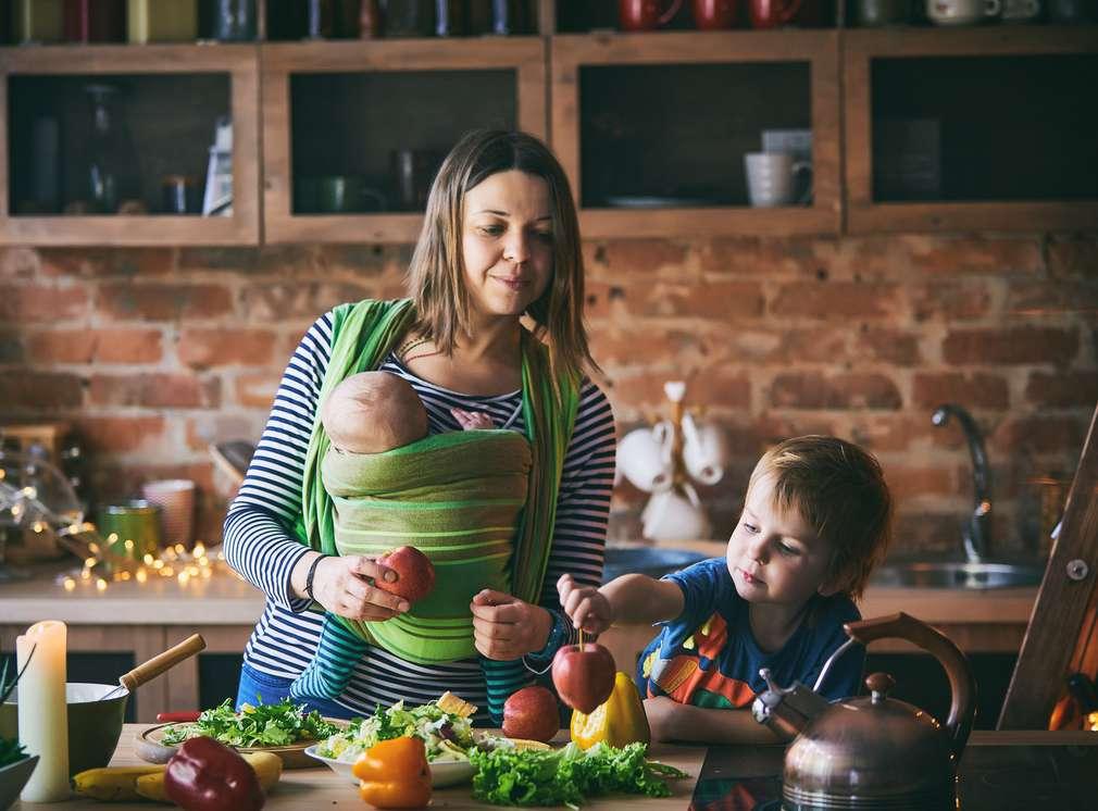 Mutter kocht mit Baby und Kind