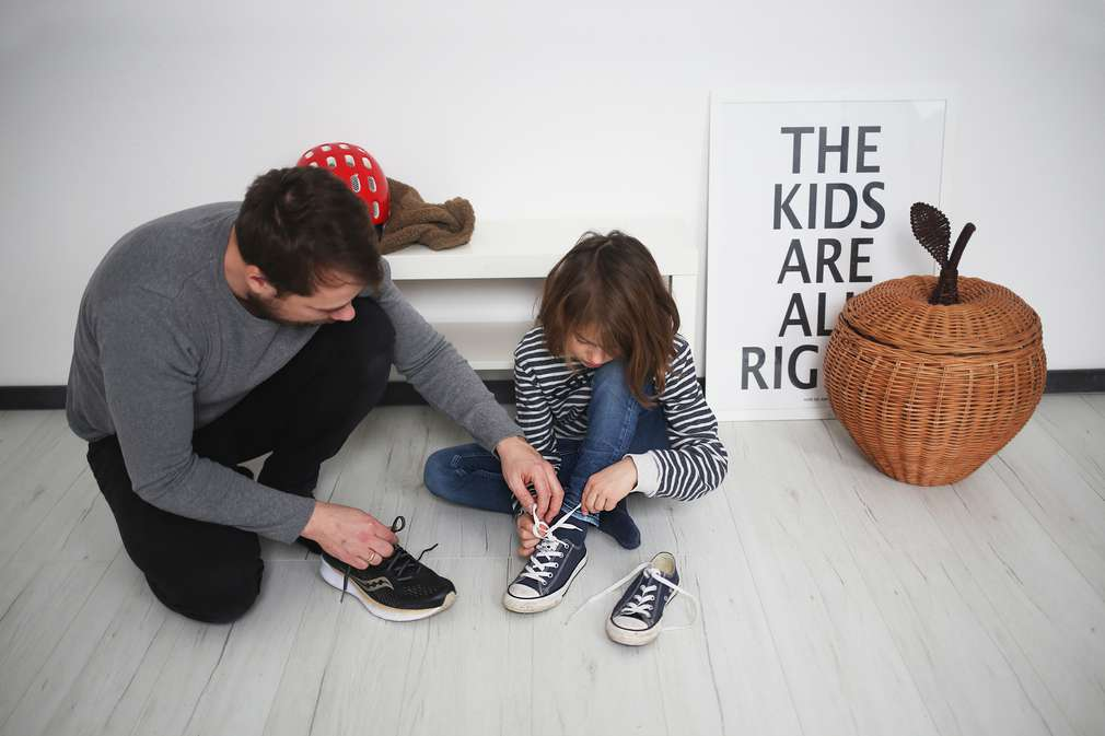 Vater und Kind binden Schuhe