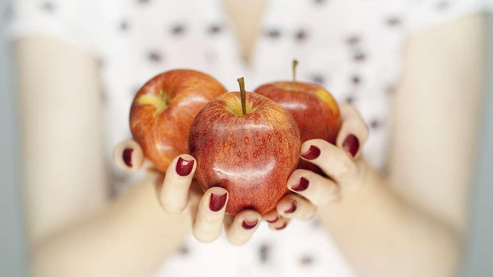 Frau hält drei Äpfel in der Hand