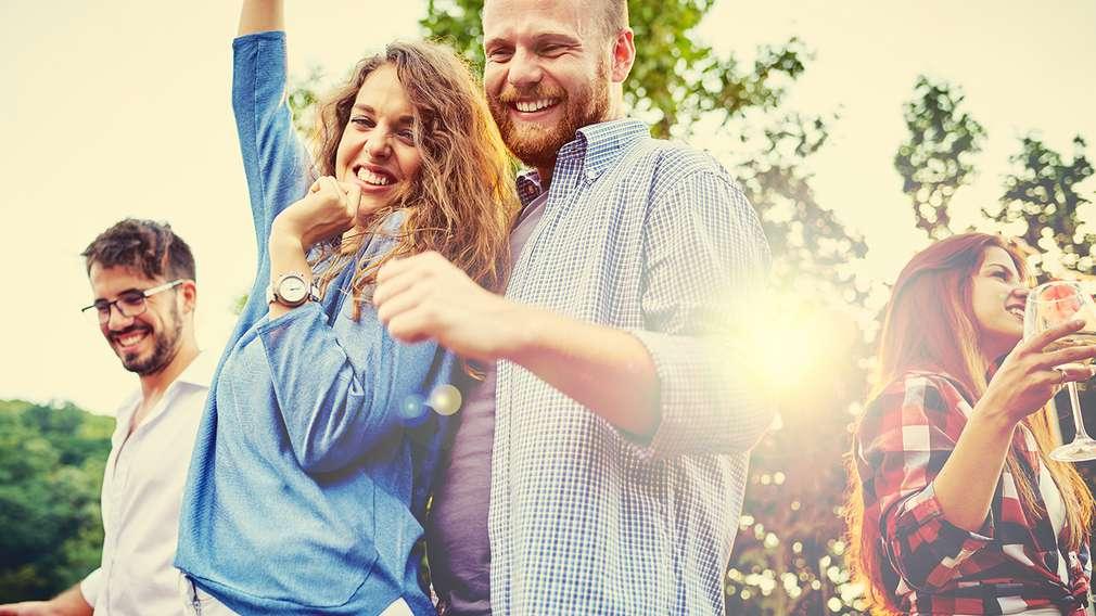 Männer und Frauen, die im Sommer im Garten eine Party feiern