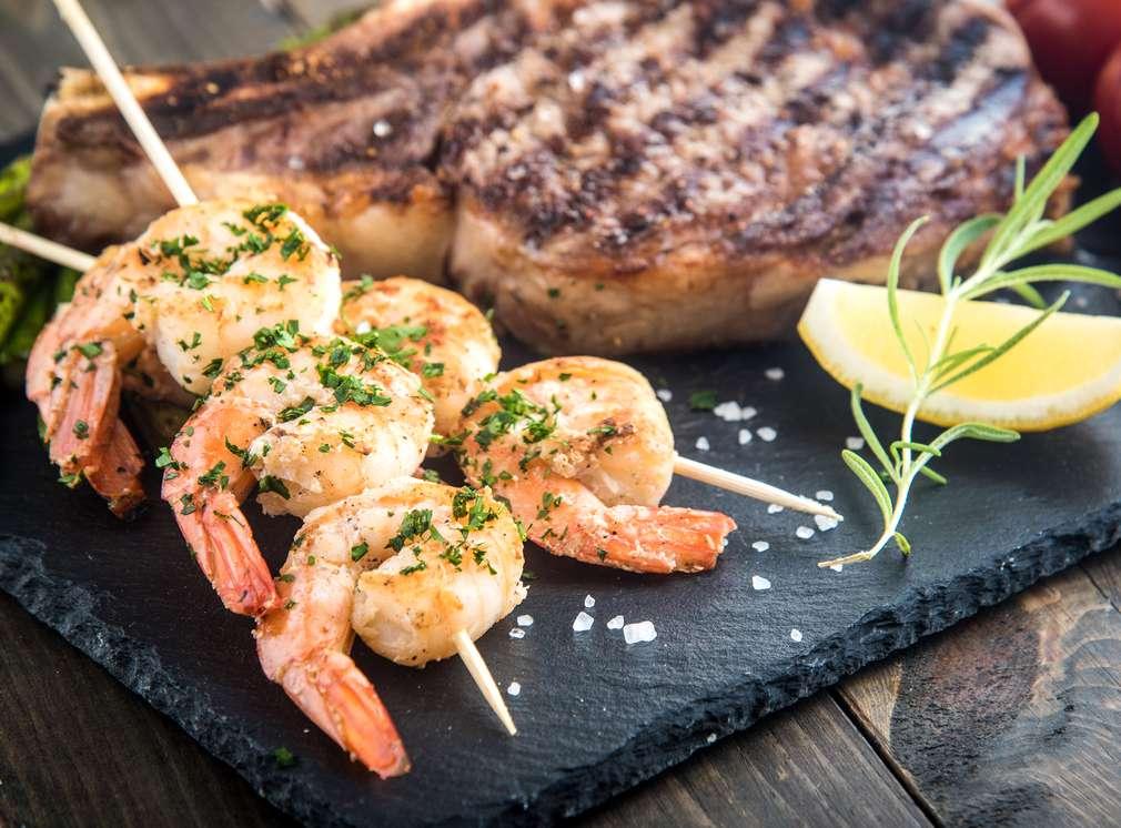 Steak und Garnelenspieße auf einer Schieferplatte serviert