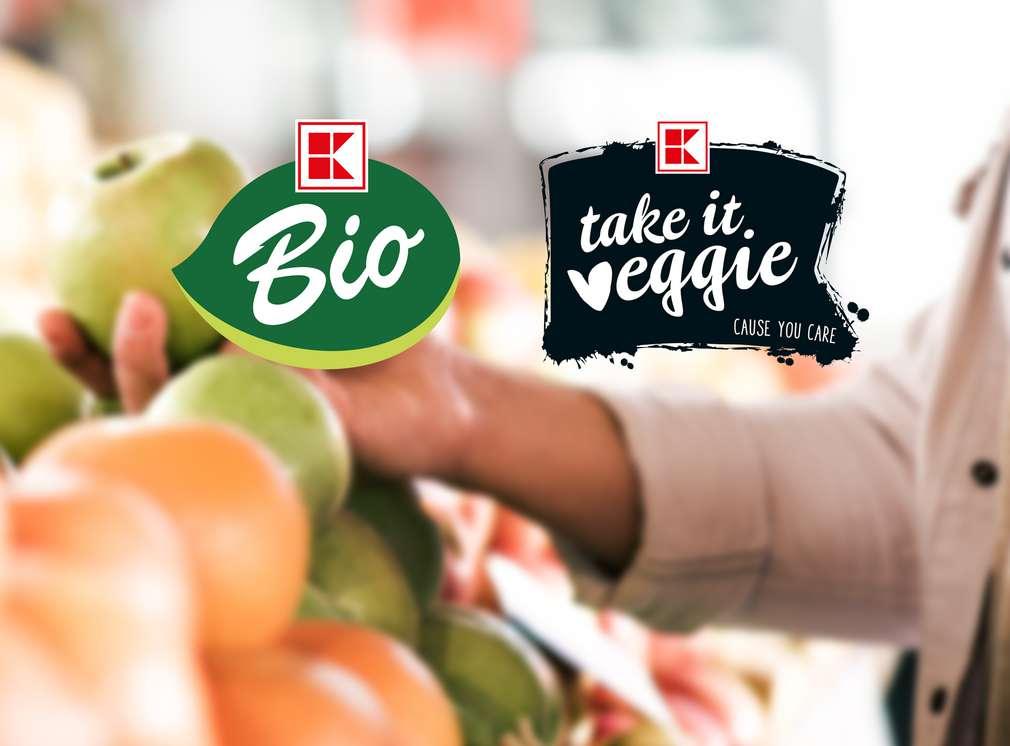 Frau nimmt Apfel aus Warenauslage; K-Bio und K-take it Veggie Logo
