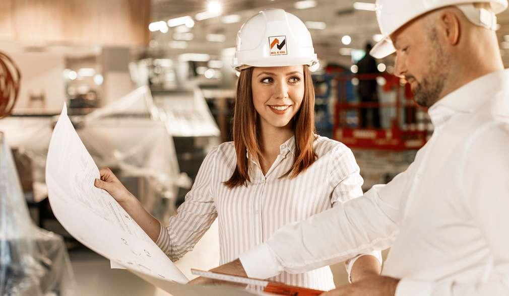 Eine duale Studentin steht in einer Neubaufiliale und bespricht den Bauplan mit einem Projektleiter.