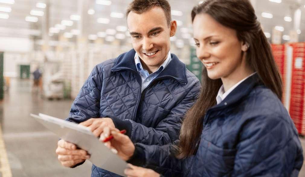 Eine duale Studentin kontrolliert mit einem Kollegen die Transportunterlagen im Logistik-Verteilzentrum.