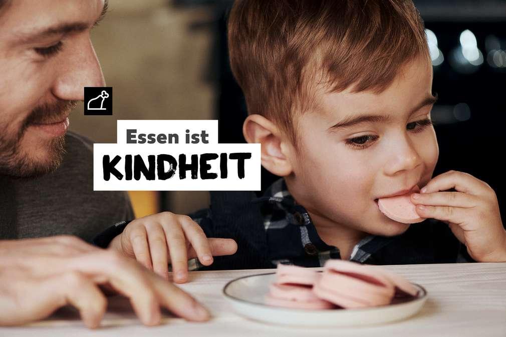 Essen ist Kindheit: Kind mit Wurstscheibe