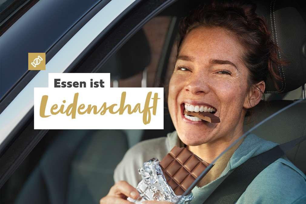 Essen ist Leidenschaft: Frau mit abgebissener Schokoladentafel