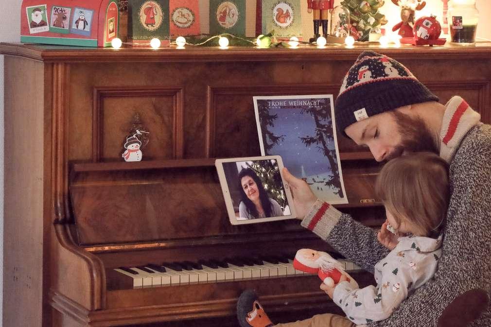 Vater und Kind telefonieren per Tablet mit der Oma