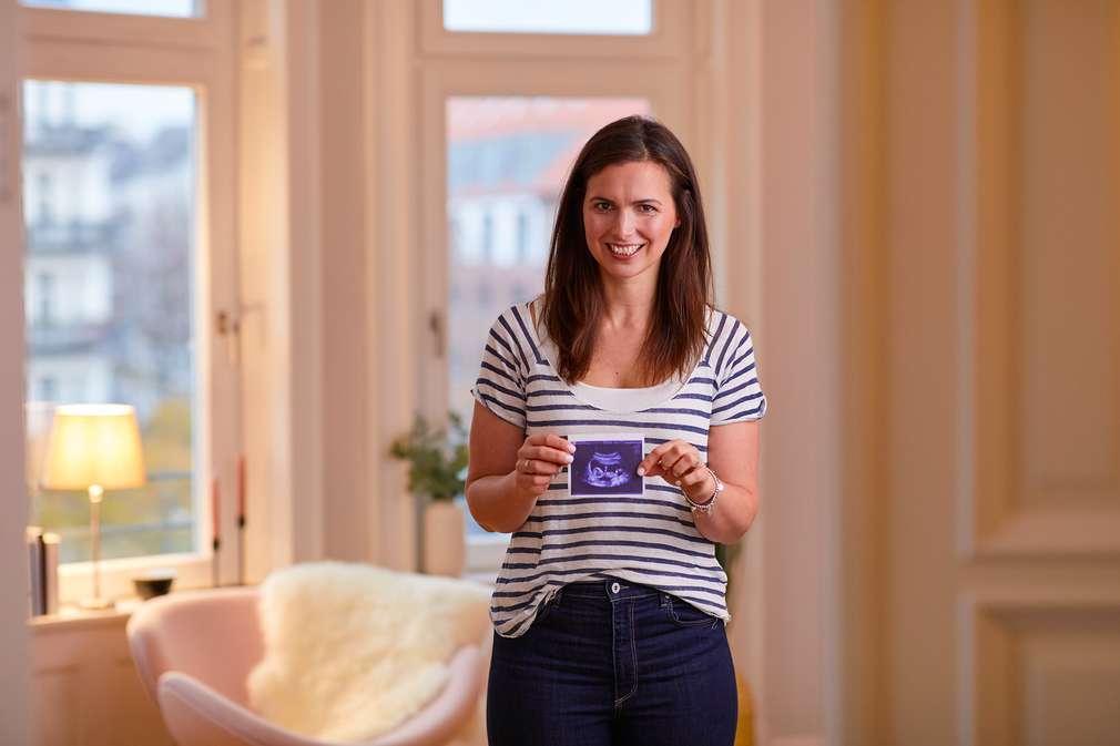 Frau mit Ultraschallbild in der Hand