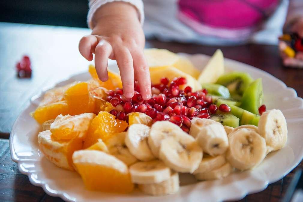 Kind greift zu Obst auf einem Teller