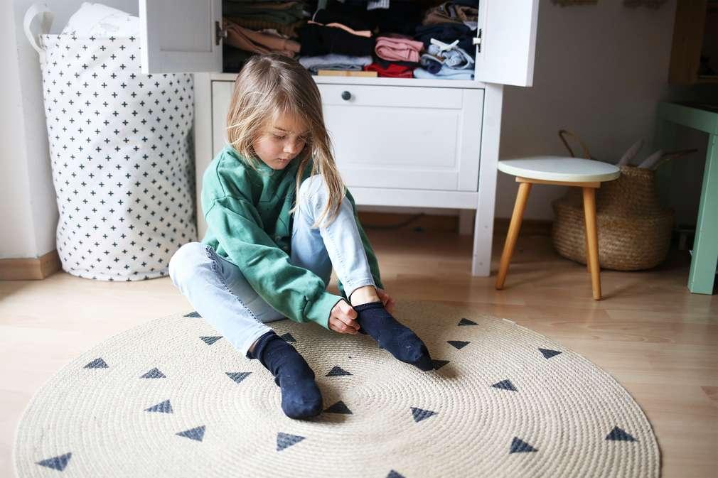 Junge bindet sich die Schuhe zu