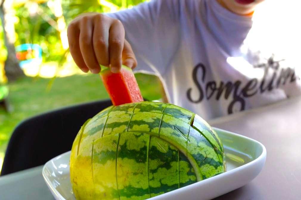 Kind greift nach einem zugeschnittenen Melonenstück