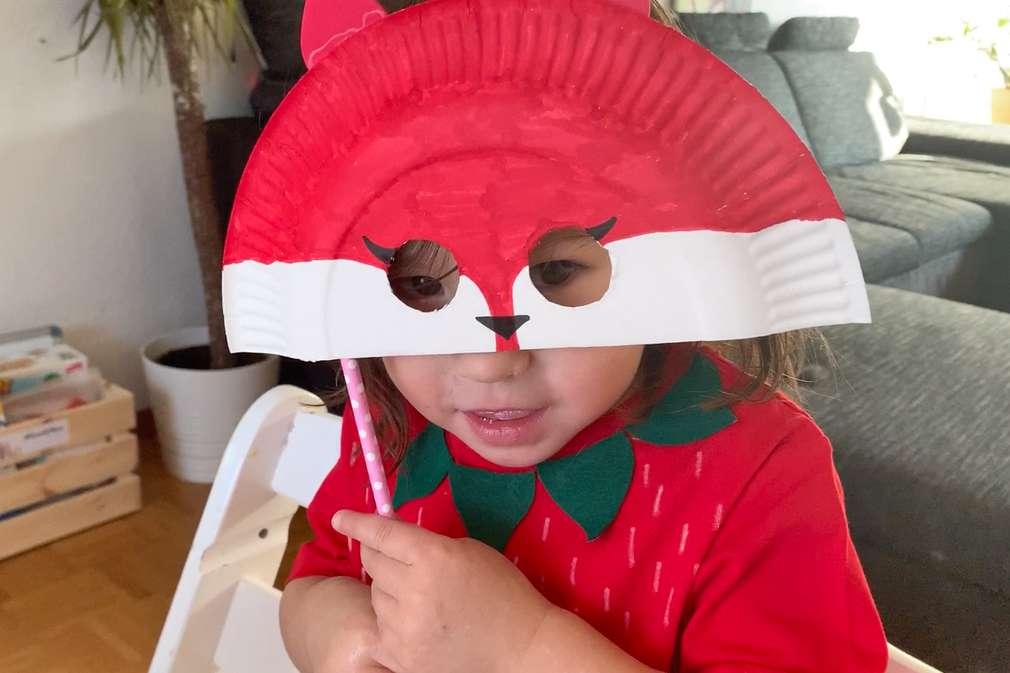 Kind hält eine Faschingsmaske hoch