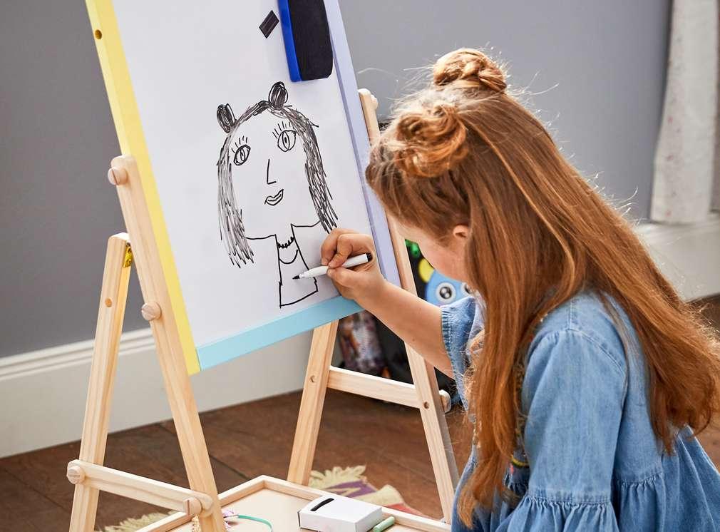 Mädchen zeichnet auf Staffelei