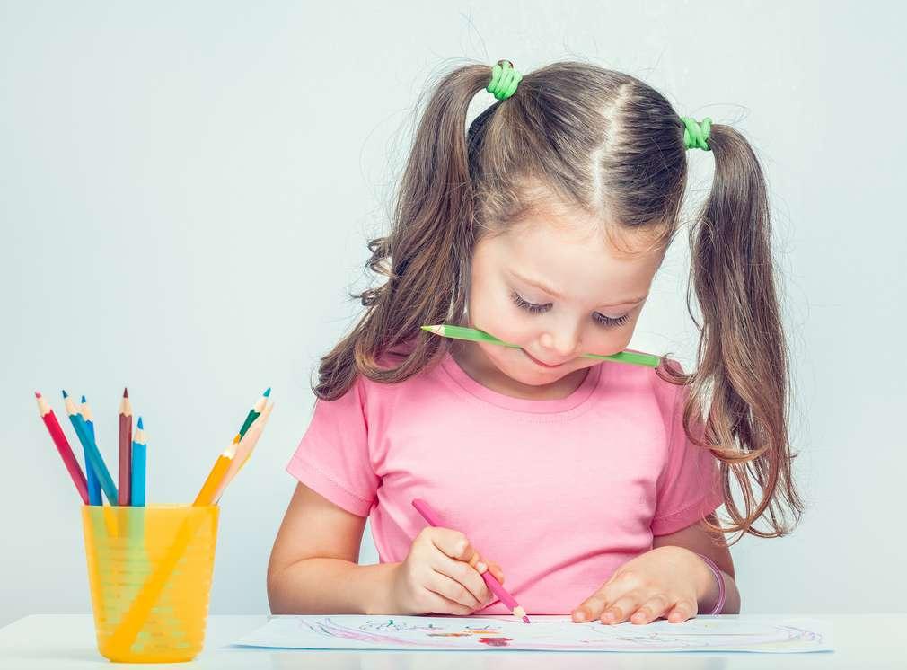 Mädchen mit Stift im Mund zeichnet