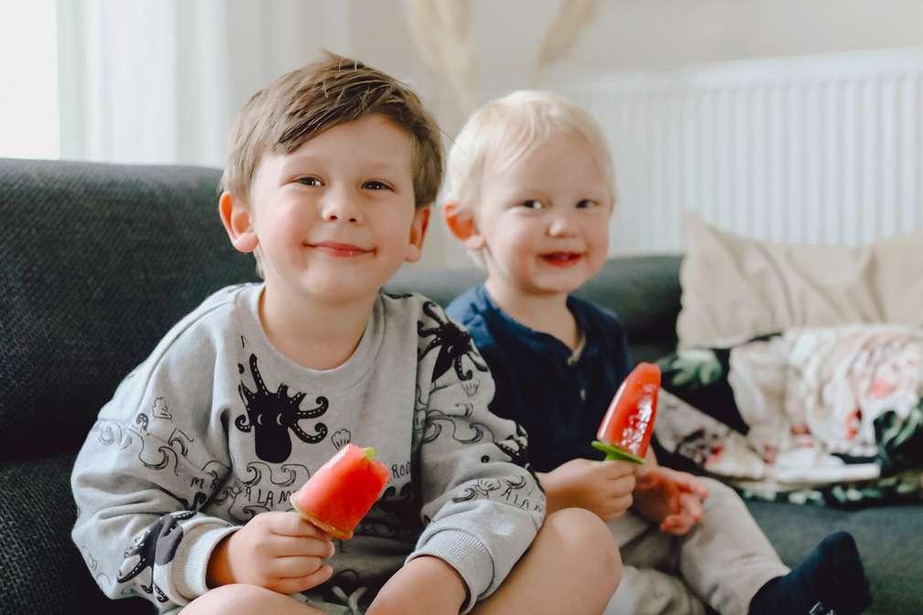 Zwei Kinder sitzen lächelnd auf dem Sofa und halten selbst gemachtes Eis in der Hand