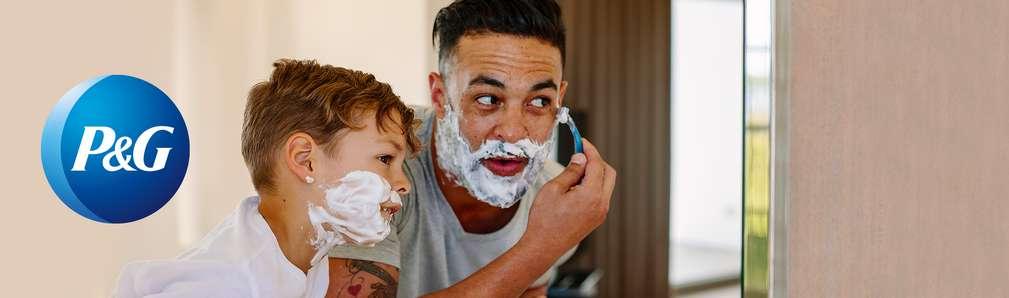 Mann mit Kind im Badezimmer: Mann rasiert sich, Kind hat Rasierschaum im Gesicht