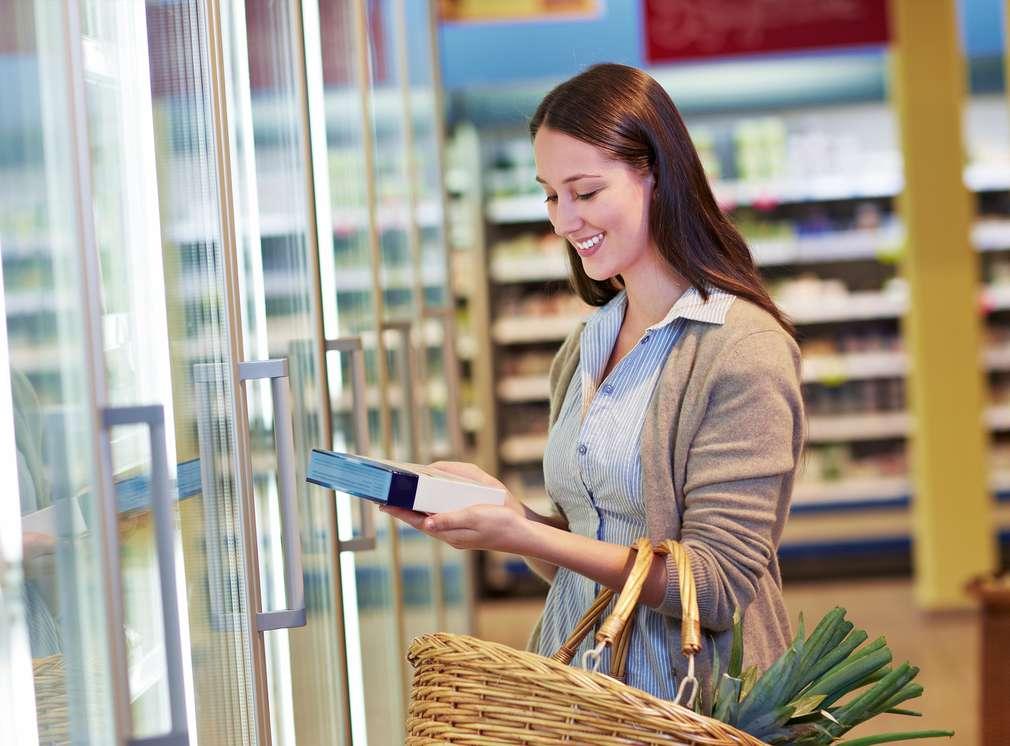Frau mit Einkaufskorb steht vor Kühlregal und hält Artikel in der Hand